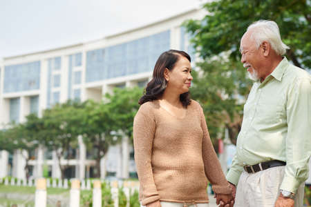 Senior Asian  man and woman holding hands and looking at each other