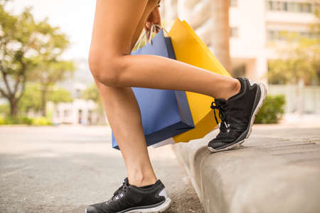 Legs of girl with shopping bags walking outdoors