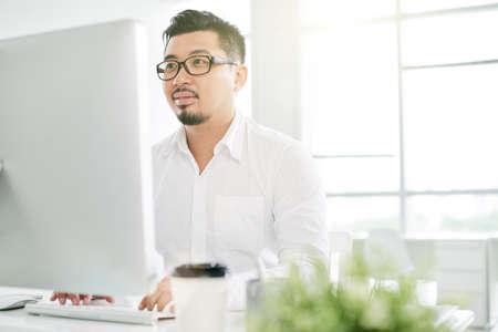 Vietnamese coder die aan manuscript in bureau werkt Stockfoto