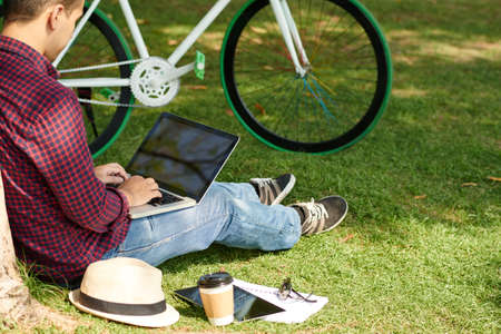 Man with laptop sitting on grass in city park Stock Photo