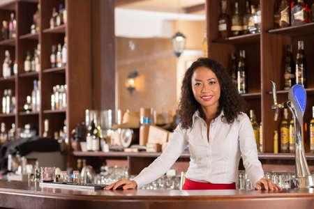 Pretty smiling Vietnamese bartender standing behind counter