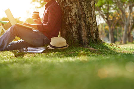 Cropped image of man sitting under the tree with coffee and laptop Stock Photo
