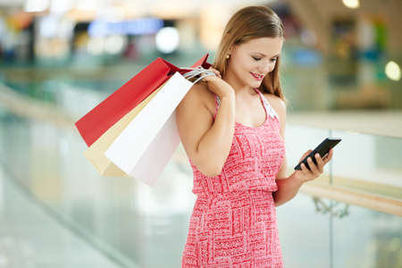 Pretty smiling woman with shopping bags reading message on her smartphone Stock Photo