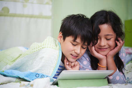 woman lying in bed: Milti-ethnic twins watching cartoon on tablet computer together