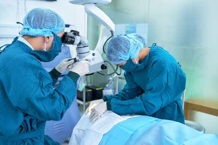 Equipo de trabajadores médicos que realizan cirugía ocular Foto de archivo - 77070667