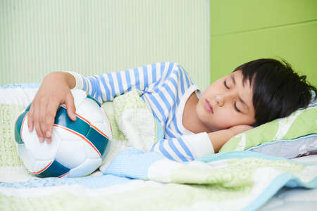 Boy sleeping in bed with soccer boy Stock Photo