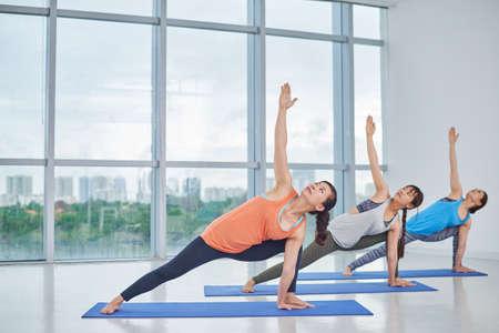Group of women doing asana to develop strength Stock Photo