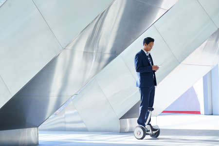 Young businessman on hoverboard standing in urban environment
