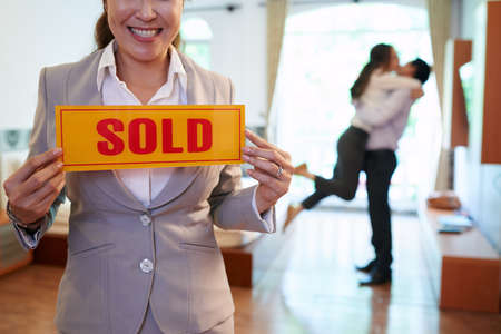 Happy real estate agent holding sold sign