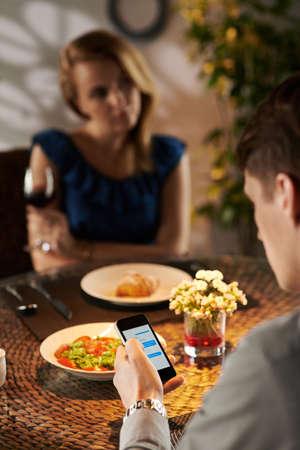 irrespeto: Hombre de mensajes de texto durante la fecha en la cafetería, ver por encima del hombro