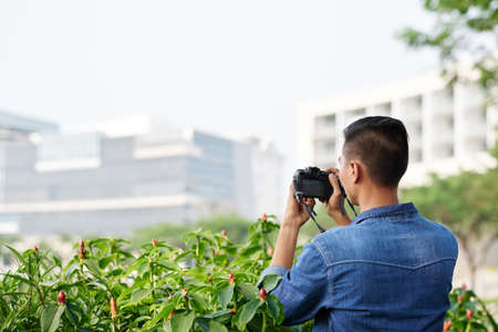 spying: Man enjoying photographing plants in the city Stock Photo