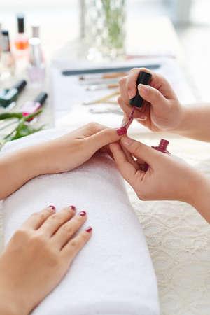 Beautician applying second coat of nail polish