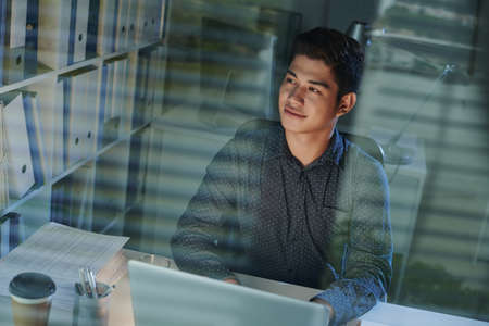 Portrait of smiling young office worker at his desk