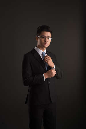 cuff: Portrait of Vietnamese business executive buttoning up cuff Stock Photo