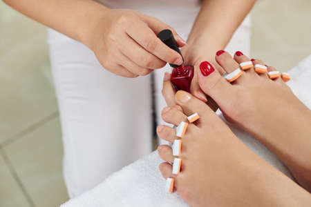 Master applying red nail polish to toenails