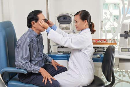 Nurse testing vision of senior patient