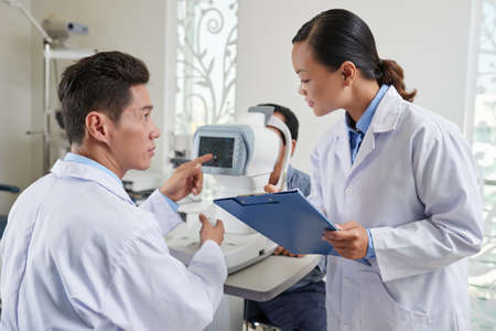 Ophthalmologist giving instructions to nurse when examining patient Stock Photo