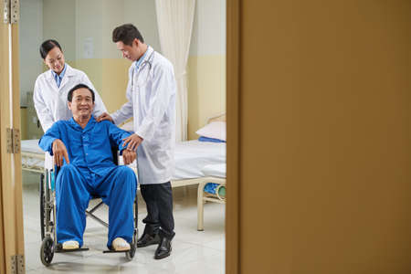Happy mature Vietnamese man in wheelchair after operation Stock Photo