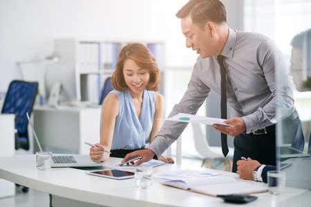 Businessman explaining data in document to his female colleague