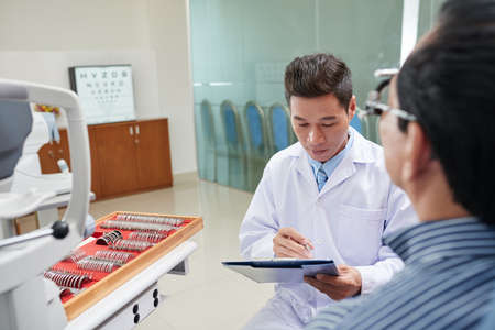 Vietnamese optometrist reading medical card of male patient Stock Photo