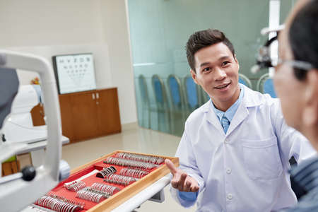 Cheerful optometrist telling good news to his patient