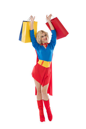 Happy excited superwoman raising with shopping bags Stock Photo