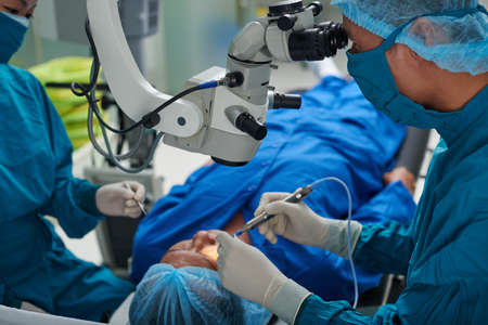 Doctor performing eye surgery in modern clinic