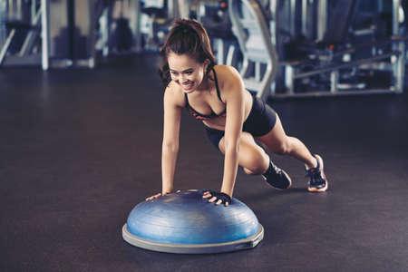 Cheerful Asian woman training with bosu ball Stock Photo