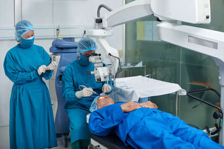 Surgeon and his assistant performing operation  on eye