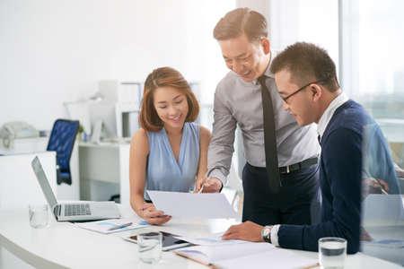 Vietnamese business team analyzing information in document