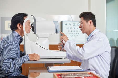 눈 검사 장비 작동 방법 수석 남자를 설명하는 의사 스톡 콘텐츠