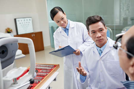 Nurse taking notes when ophthalmologist talking to patient Stock Photo