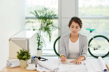 Young female architect working on blueprint in light office