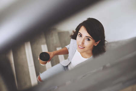 Beautiful woman looking at camera when standing on stairs Reklamní fotografie