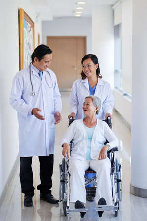 Vietnamese doctor and nurse walking with patient in wheelchair
