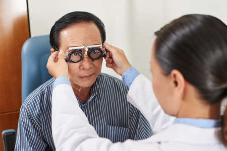 Female ophthalmologist precisely determines diopter for senior man 스톡 콘텐츠