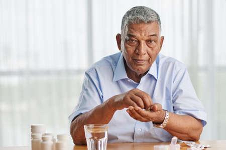 Portrait of elderly Indian man taking medicine every day