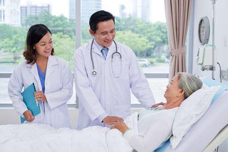 Vietnamese arts en verpleegster die aan hogere patiënt in afdeling spreken