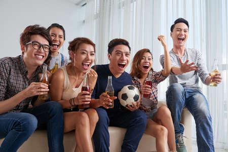Jóvenes vietnamitas animando para su equipo de fútbol favorito Foto de archivo - 77184721