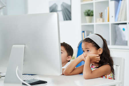 Two Indonesian children sitting in front of computer in office