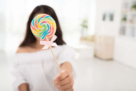Young woman covering her face with lollipop, selective focus Stock Photo
