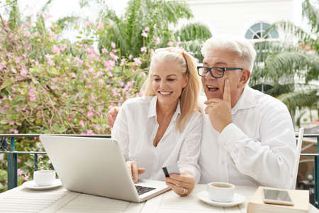 Cheerful mature couple shopping online in cafe