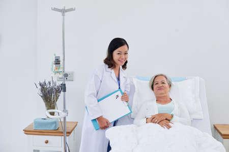 Portret van verpleegster en hogere vrouwelijke patiënt in bed Stockfoto - 77186030