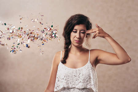 Young woman pretending to shoot herself, sparkles falling out of her head Stock Photo
