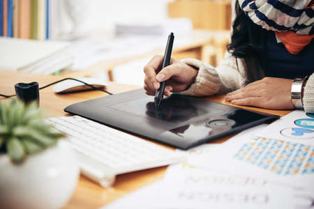 editor: Female hand drawing on the graphic tablet in office