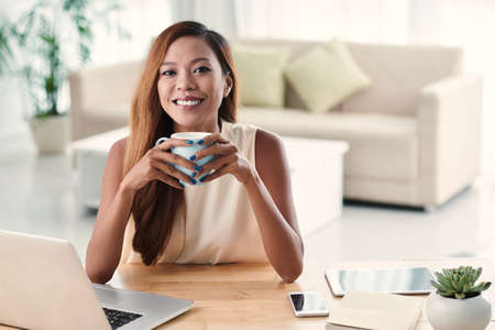 Portrait of beautiful Filipino girl holding cup of hot chocolate Stock Photo