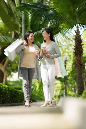 Joyful mature women walking and chatting outdoors after shopping