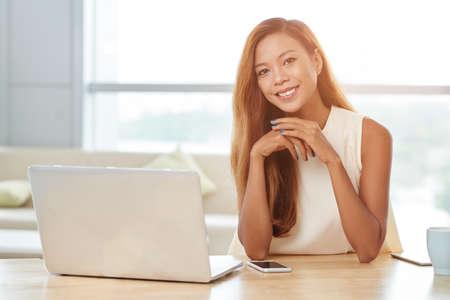 彼女の職場で座っているフィリピン人の若い女性の肖像画 写真素材