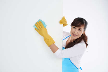 Asian woman wiping white wall with wet cloth