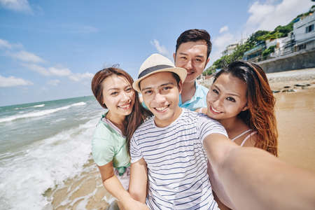 Asian smling young people taking selfie at the beach Banco de Imagens
